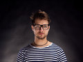 Man in striped t-shirt and eyeglasses against black background. Royalty Free Stock Photo