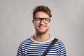 Man in striped t-shirt and eyeglasses against gray background. Royalty Free Stock Photo