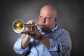 Man with strong expression plays a trumpet and focused playing studio shot grey background Stock Images