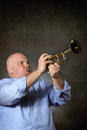Man with strong and focused expression plays a trumpet studio shot grey background Royalty Free Stock Photo