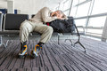 Man stuck at airport image of bearded hippy style dressed person sleeping on travel backpack inside waiting lounge sitting black Royalty Free Stock Photo