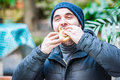 Man stuffing his face with a hamburger