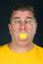 Man sucking on lemon a sucks a very sour slice and makes a funny face due to the tart flavor Stock Photo
