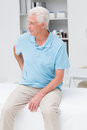 Man suffering from backache in clinic senior while sitting on bed Royalty Free Stock Photo