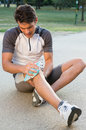 Man suffering pain knee young male athlete sitting on ground and taking ice for Stock Image