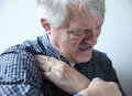 Man suffering from shoulder pains older grimaces and touches area of pain in his Royalty Free Stock Image