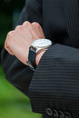 Man in suit checking the time on designer watch Stock Photos