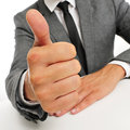 Man in suit giving a thumbs up signal wearing sitting table Stock Photography