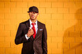 Man in suit holding coat by yellow wall a young a with a red tie and hat standing front of a Royalty Free Stock Image