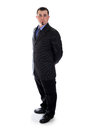 Man in suit holding his hands behind back a a dark grey Stock Photography