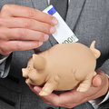 Man in suit introducing a euro bill in a piggy bank closeup of wearing Royalty Free Stock Photos