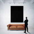 Man in  suit looking at black poster holding on the white brick wall. Classic sofa, wood floor. Vertical Royalty Free Stock Photo