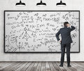 Man in suit looking at whiteboard with formulas Royalty Free Stock Photo