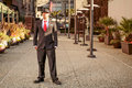 Man in suit in outdoor business park a young a with a red tie and hat standing front of alley Stock Photography