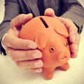 Man in suit with a piggy bank wearing sitting desk his hands Royalty Free Stock Photos
