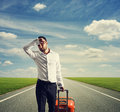 Man with suitcase on a road weary businessman Stock Photos