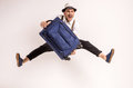Man with suitcase young creative is posing on grey background Stock Photography