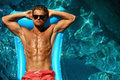 Man Summer Fashion. Male Model Tanning By Pool. Skin Tan Royalty Free Stock Photo