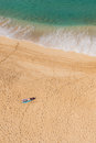 Man sun bathing solo on secluded beach view of a from high above Royalty Free Stock Images