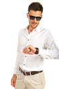 Man with sunglasses checking time young to his wristwatch isolated on white background Royalty Free Stock Photography