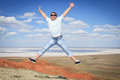 Man in sunglasses jumping over blue sky young Stock Images