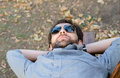 Man with sunglasses lying on bench Stock Photos