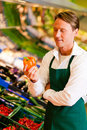 Man in supermarket as shop assistant Stock Photography