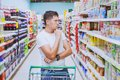 Man in the supermarket, customer thinking, choose what to buy Royalty Free Stock Photo