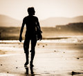 Man with surfboard silhouette of the walking on the beach the Stock Images