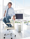 Man surfing his office chair and smiling in modern Royalty Free Stock Image