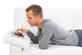 Man surfing internet young on the couch with tablet pc Stock Photos