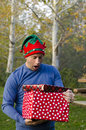Man surprised by the two Christmas gifts he is holding. Royalty Free Stock Photo