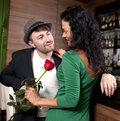 Man surprising girlfriend with flower the young fashionable men in a hat and its on appointment in cafe Royalty Free Stock Images
