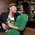 Man surprising girlfriend with flower the young fashionable men in a hat and its on appointment in cafe Royalty Free Stock Photo