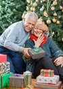 Man surprising senior woman with christmas gifts happy men covering s eyes while her in store Stock Photos