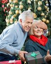 Man surprising woman with christmas gifts in store happy senior men covering s eyes while her gift Stock Photos