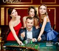 Man surrounded by girls gambles roulette Stock Image