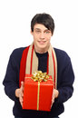 Man with sweater and scarf giving you a big Christmas gift. Royalty Free Stock Photo