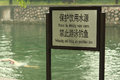 Man is swimming near sign swimming forbidden in beijing Royalty Free Stock Photos