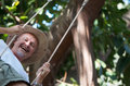 Man on swing summer fun with laughing mature wearing cowboy hat a natural green and leafy outdoor setting Royalty Free Stock Photos