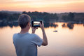 Man with tab makes photo of the sunset background Stock Images