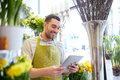 Man with tablet pc computer at flower shop Royalty Free Stock Photo