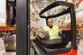 Man with tablet pc operating forklift at warehouse Royalty Free Stock Photo