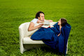 Man take care about his girlfriend on the couch green field Stock Photos