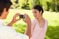 Man takes a photo of his friend while she poses Stock Photo