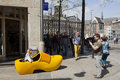 Man takes picture of woman in giant yellow clog in amsterdam on dam square Stock Photography