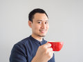 Man takes a sip of coffee in red cup.
