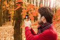 Man taking autumn outdoor photo with mobile phone forty years old caucasian enjoying nature and modern technology Stock Image