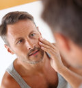 Man taking care skin in bathroom applying cosmetics on his face Royalty Free Stock Image