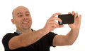 Man taking cellphone photo middle age a with a or smartphone white background Stock Photography